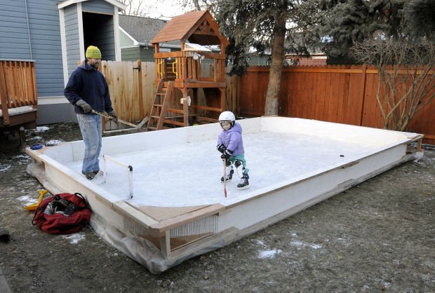 Tim Wright and his daughter Hazel, 3, play on the ice rink in the backyard  of their Missoula home recently. The family's homemade ice sheet may be one  of ... - Backyard Ice: Homemade Skating Rinks Pop Up Around Missoula