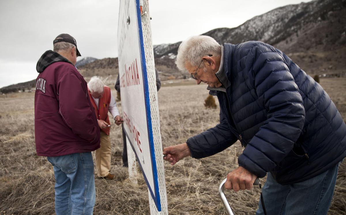 Raising a sign at the veterans home site