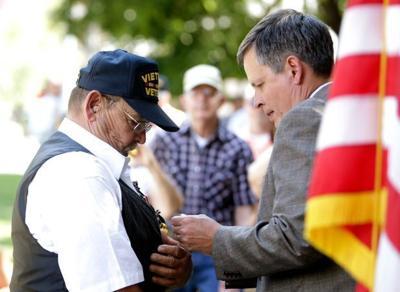 U.S. Sen. Steve Daines pins a medal on Vietnam veteran Rick Ketterling