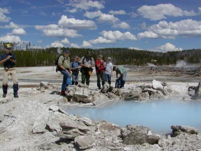 The crew who installed the seismic instruments admire the Porkchop Geyser pool.