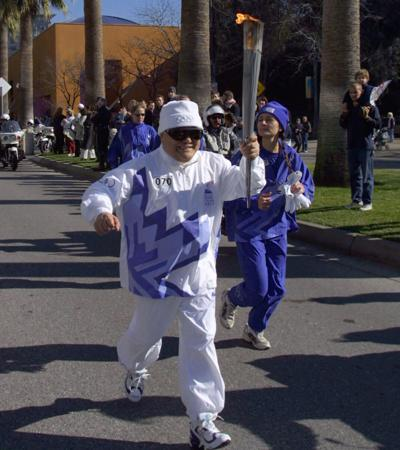 Torchbearer Yosh Uchida carries the Olympic Flame during the 2002 Salt Lake Olympic Torch Relay in San Jose, California.