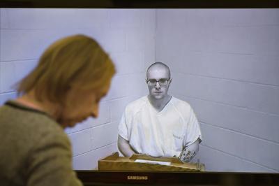 Kaleb Taylor, 21, center, appears via video