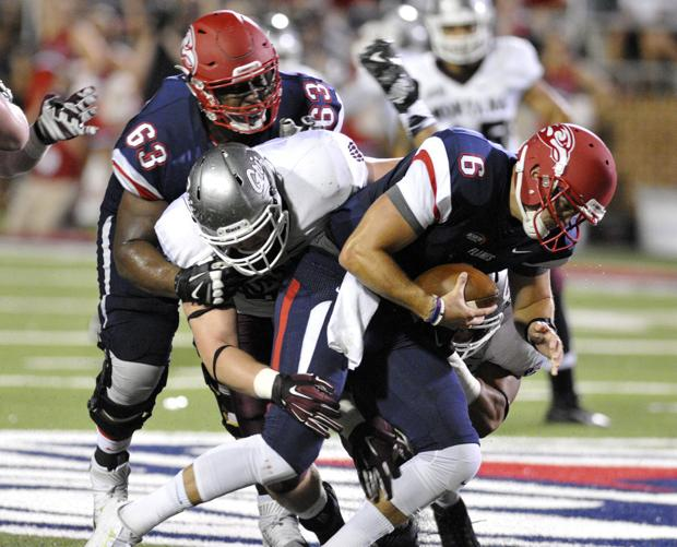 Montana's Caleb Kidder, center, tackles Liberty quarterback Josh Woodrum while being pressured by Liberty's Jonathan Burgess during the Grizzlies' 31-21 loss on Saturday at Williams Stadium in Lynchburg, Va. (Tom Bauer/The Missoulian)