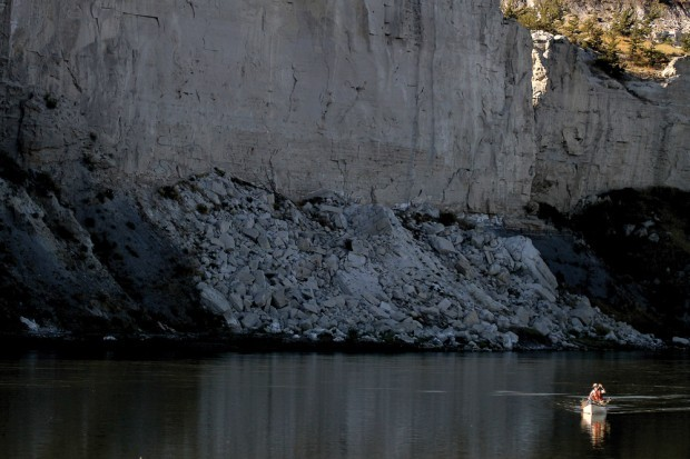 A canoe glides past a canyon wall