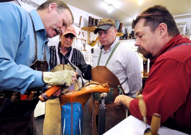 Master boot maker Dan Schwarz, left, demonstrates how to welt a boot