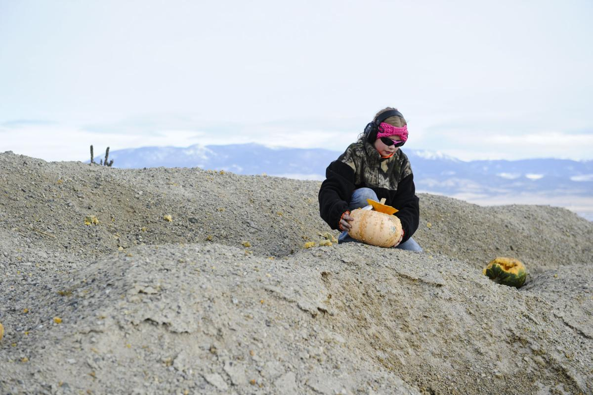 Tobey Peck, 11, places her Tannerite filled pumpkin down range Saturday.