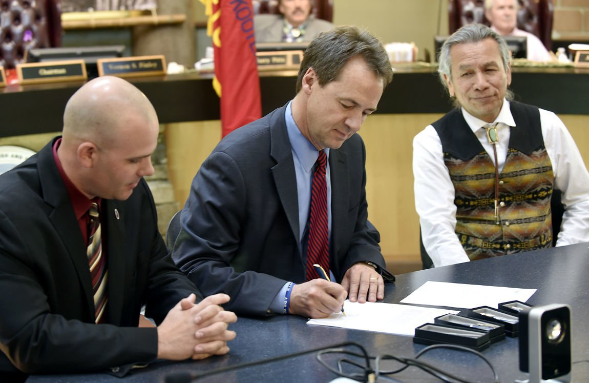 Gov. Steve Bullock, center, signs the water compact in the Tribal Council Chambers in 2015