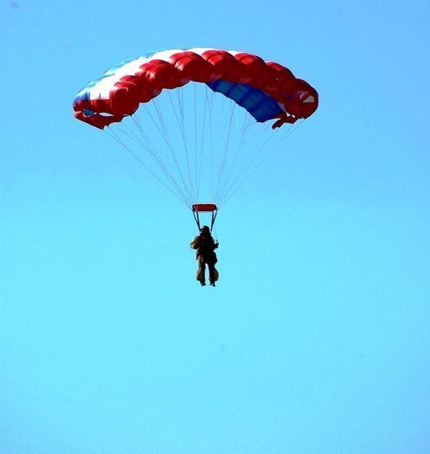 A smoke jumper parachutes toward BLM land