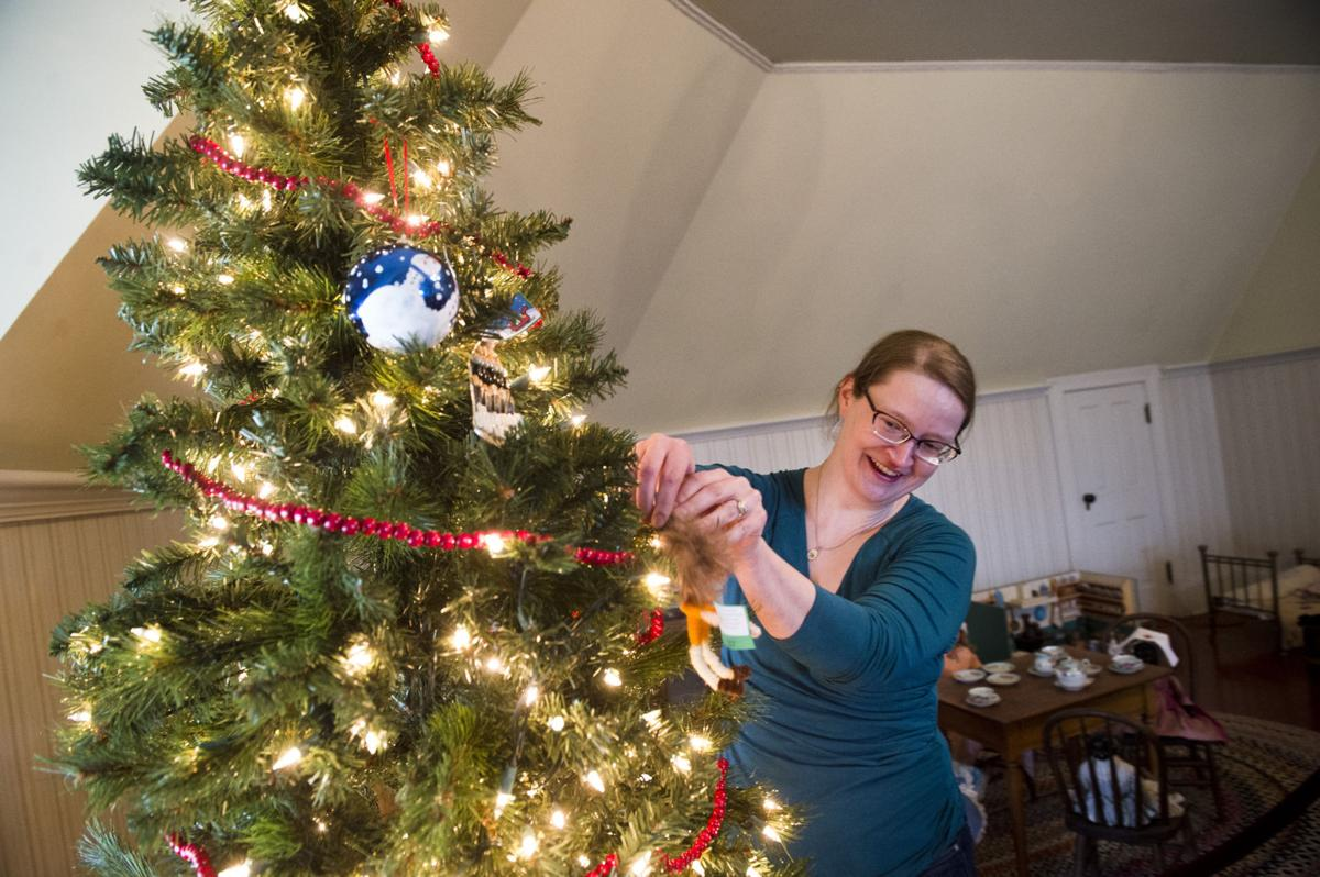"""Maggie Ordon, curator of history for Montana Historical Society, decorates a tree in the Original Governor's Mansion last week while setting up for the """"Home for the Holidays"""" exhibit at the mansion."""