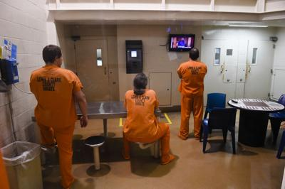 Inmates use the phone and watch television in the Lewis and Clark County Detention Center