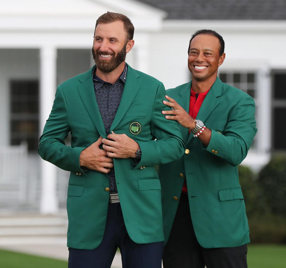 Tiger Woods presents Dustin Johnson with his green jacket after he won the Masters at Augusta National Golf Club on Sunday, November 15, 2020, in Augusta, Georgia.