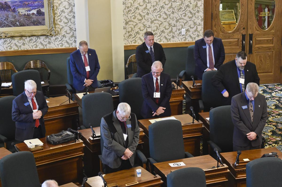 Maskless Republican senators bow there head's in prayer during Wednesday's caucus meeting.