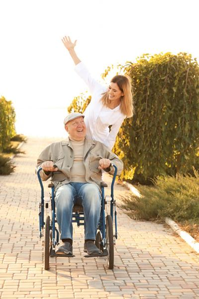 Nurse from care home and senior man in wheelchair walking outdoors