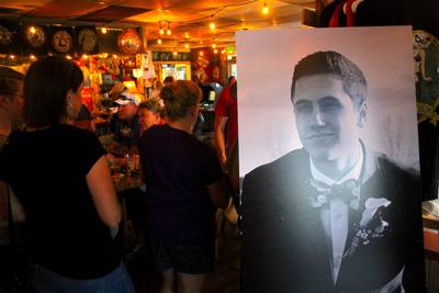A picture of Connor Imus hangs in the entrance of a busy Horsefly Brewing