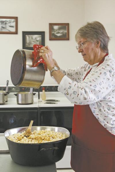 Betty-Ann McCluskey pours hot caramel into freshly popped corn