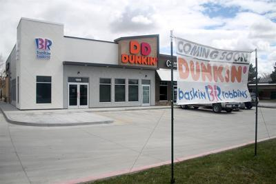 A coming soon sign stands in front of the incoming Dunkin' Donuts
