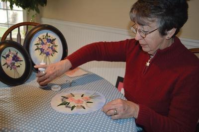 Wendy Burrell works on some pressed flower designs