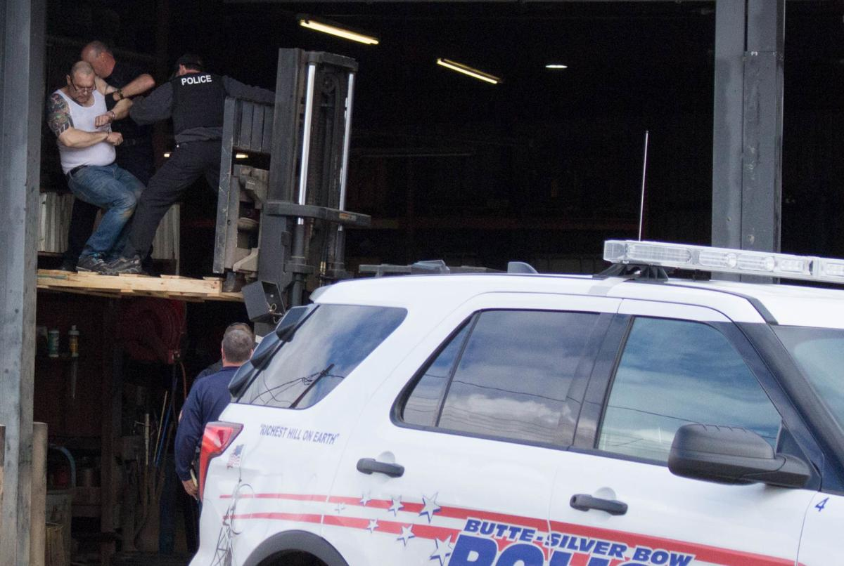 Police use forklift to bring man down from elevated tire storage platform