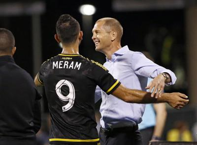 Columbus Crew coach Gregg Berhalter hugs forward Justin Meram (9) after he subbed out during the second half against the Chicago Fire at Mapfre Stadium in Columbus, Ohio, on Saturday, Aug. 12, 2017.