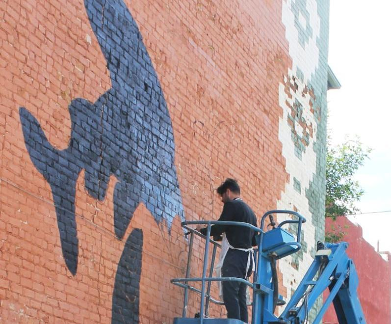 LEAD PHOTO: Mark Gettings and family dog Keely check out son Roger Peet's mural