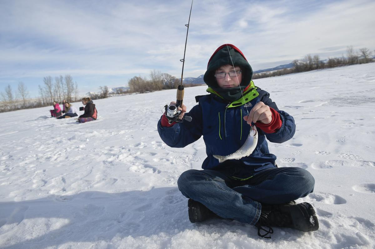 East Valley Middle School student Derek Price grips a kokanee salmon Thursday morning at the Helena Valley Regulating Resevoir.