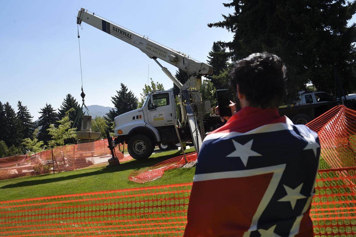 Tony Crew, with a Confederate flag draped over his shoulders, films the removal of the Confederate Fountain from Hill Park Friday afternoon.