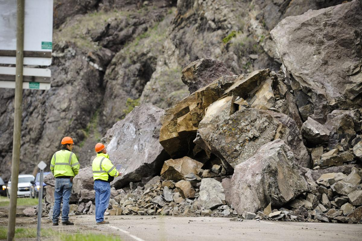 Montana Department of Transportation crews work to clear a substantial rockslide