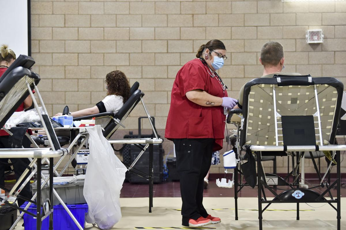 Adrienne Loves, center, draws blood from MSGT Michael Touchette on Wednesday at a Red Cross blood drive on Fort Harrison.