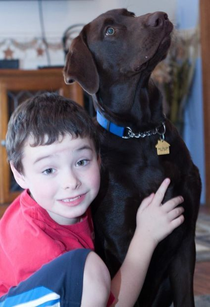 Levi Balentine, 8, and Bridger the service dog who has a calming effect on him