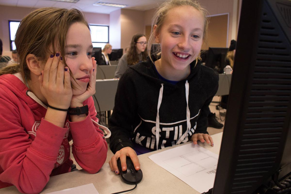 Girls work to decode cryptograms during recent GEMS Club meeting