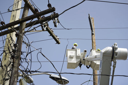 A brigade from the Electric Power Authority repairs distribution lines damaged by Hurricane Maria