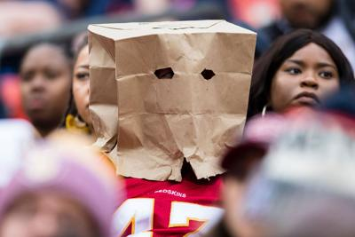 A Washington Redskins fan sits in the stands with a paper bag over their head during the second half against the New England Patriots at FedExField on Oct. 6, 2019 in Landover, Maryland.