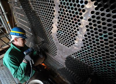 A boilermaker works replacing brass tubing