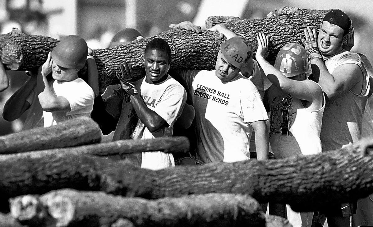 Football players assist in moving logs