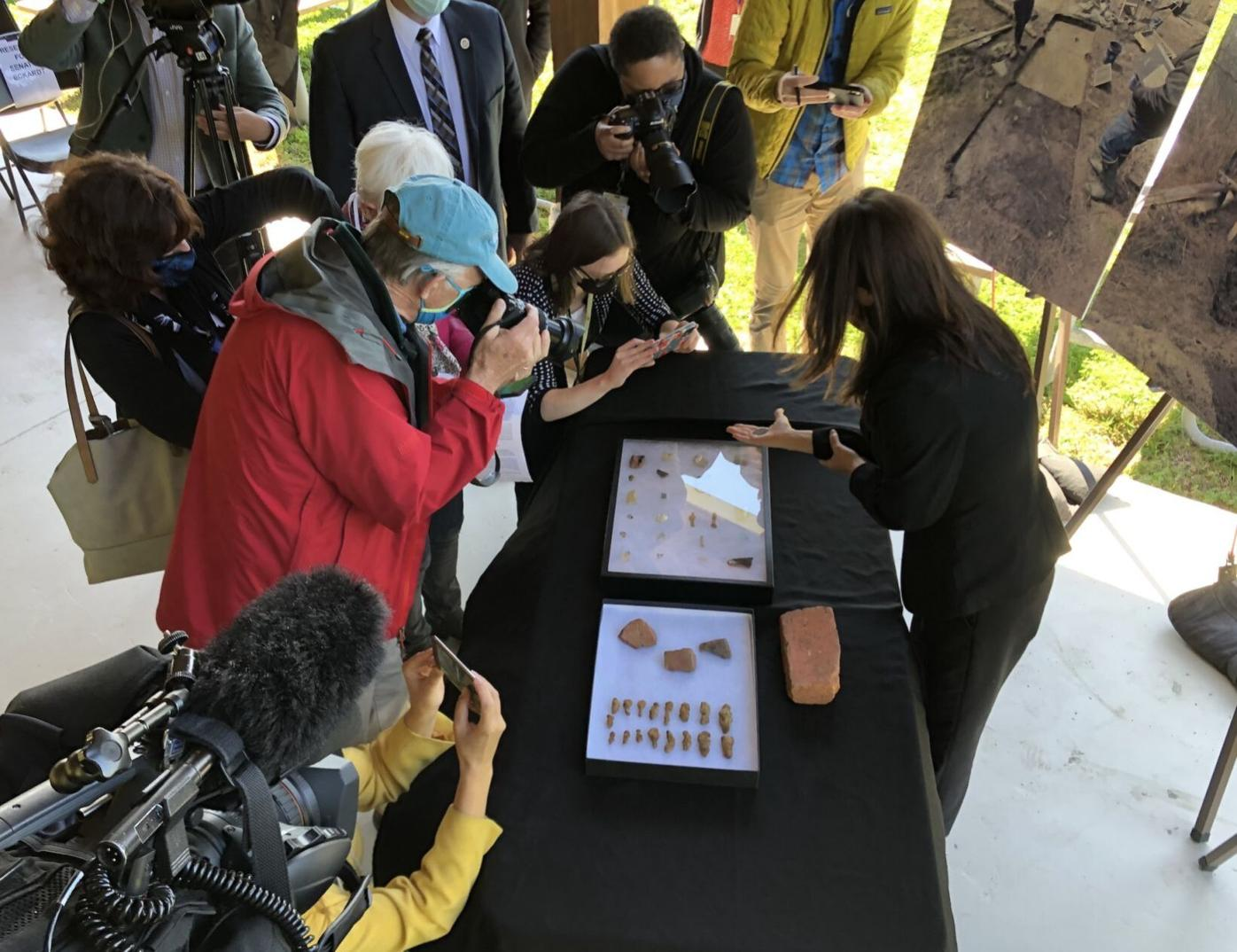 Archaeologist Dr. Julie Schablitsky shows a coin to media members