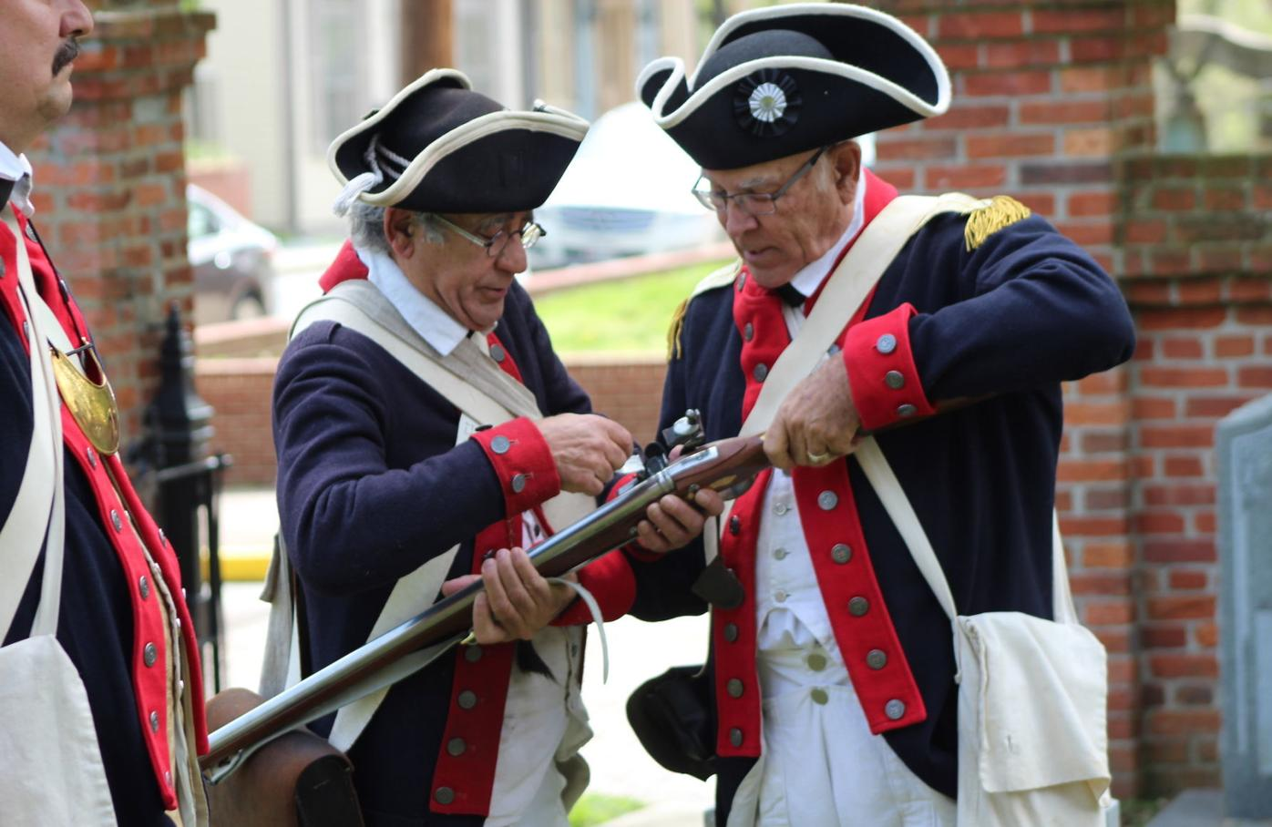 Re-enactors reload musket