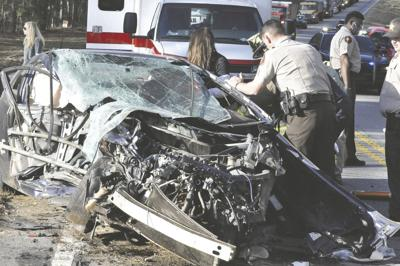 Lamar County EMT Rachel Hardeman and Sgt. Wayman Henson attend to Anthony Furlow of Forsyth as firefighters work to extricate him from his Honda Civic at the scene of a three-car collision on Hwy. 36 East at Eady Creek Road March 11. (Photo/Walter Geiger/Barnesville Herald-Gazette)