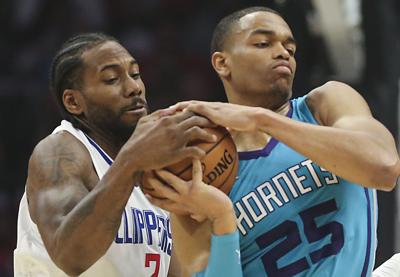 Clippers forward Kawhi Leonard tries to wrestle the ball from Hornets forward PJ Washington during their game Monday night at Staples Center.