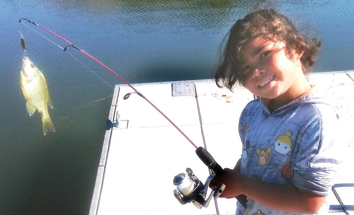 The Fishing Report: Men stoop to help child catch a bluegill