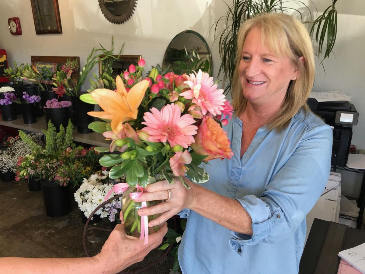 Traci Bailey, catering manager at Smoke Open Fire Cooking, receives a bouquet of flowers from an employee at BJ's Petal Pushers.