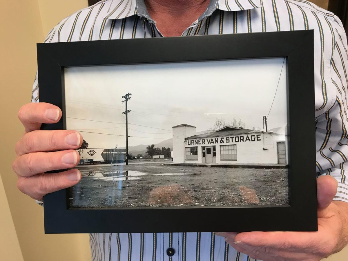 Randy Turner holds an early photo of Turner Moving & Storage.