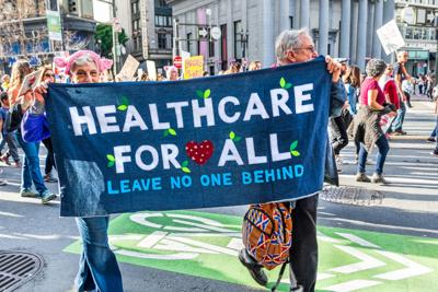 """January 19, 2019 San Francisco / CA / USA - Participants to the Women's March event carry """"Healthcare for all"""" sign while marching on Market street in downtown San Francisco"""