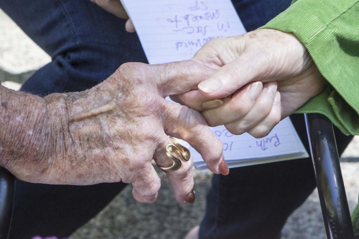Two 90-something seniors hold hands during a recent Mighty Nineties luncheon sponsored by the Molly's Angels board of directors.