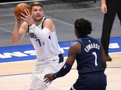 The Dallas Mavericks' Luka Doncic, left, takes a shot against the Minnesota Timberwolves' Anthony Edwards during a preseason game at American Airlines Center in Dallas on December 17, 2020.