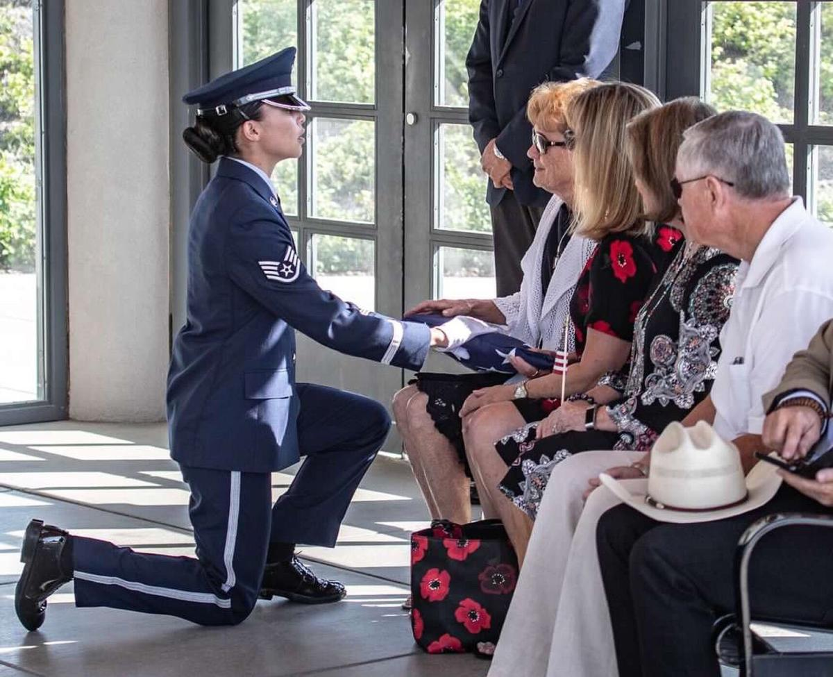 A member of the Air Force honor guard presents a flag to Susann Evans, Jennifer Huffman's mother, at his burial at Sacramento Valley National Cemetery