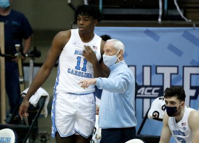 Head coach Roy Williams talks with Day'Ron Sharpe of the North Carolina Tar Heels during the first half against the Wake Forest Demon Deacons on January 20, 2021 at the Dean Smith Center in Chapel Hill, North Carolina.