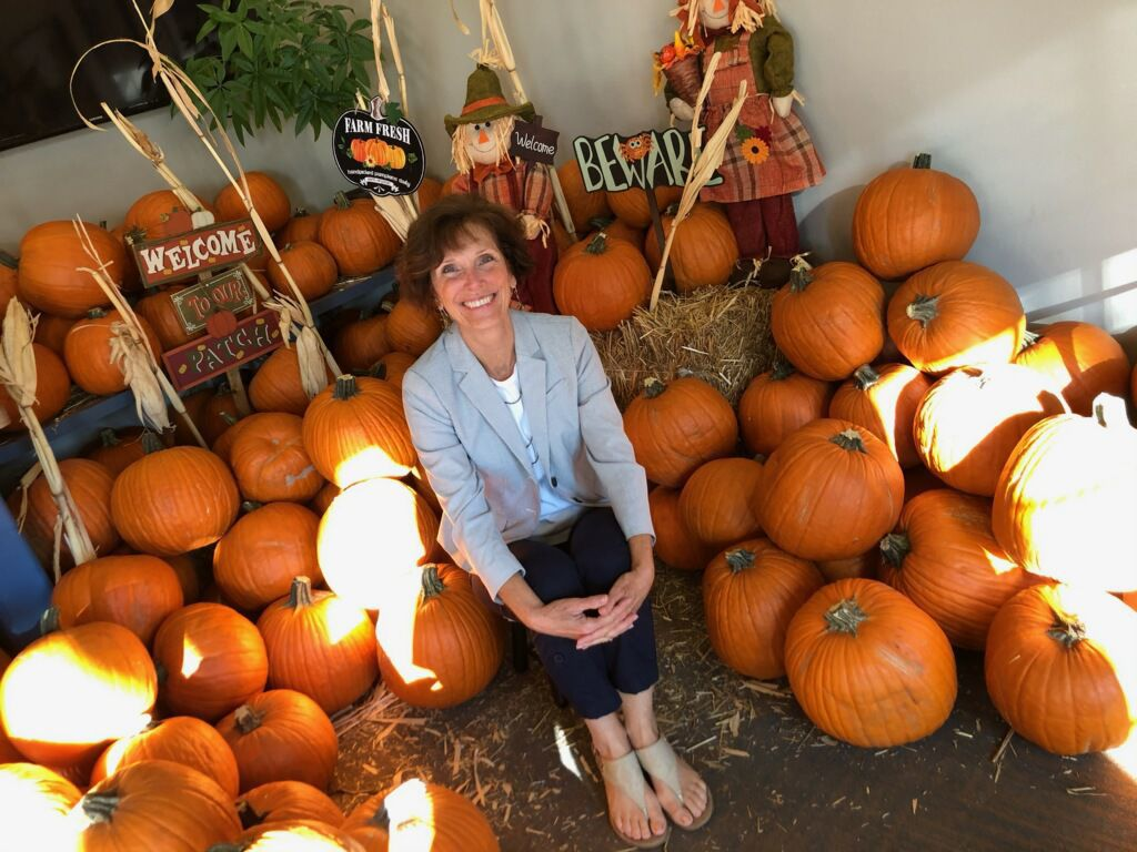 An adult patient of American Canyon Orthodontics poses in the office pumpkin patch.