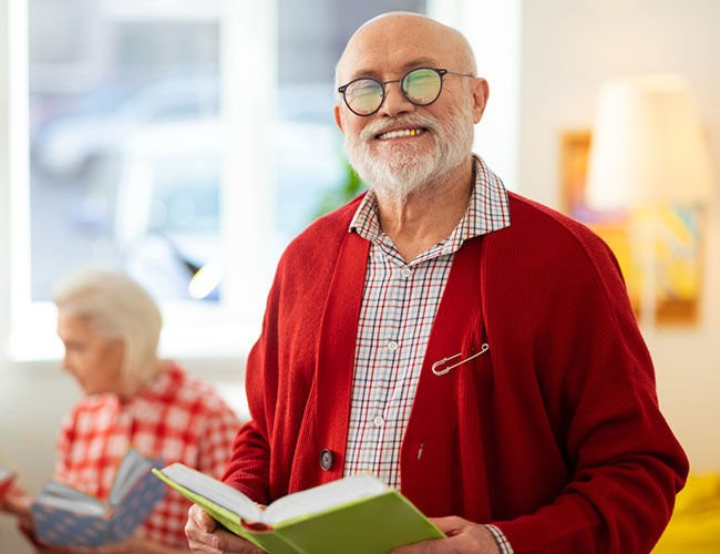 Joyful happy aged man standing with a book