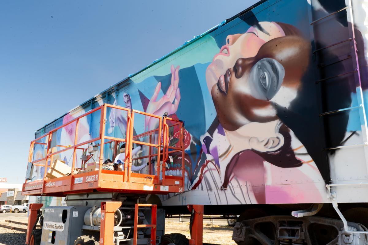 ELLE, a graffiti/street artist/muralist, works on a rail car art installation near the Wine Train car barn.