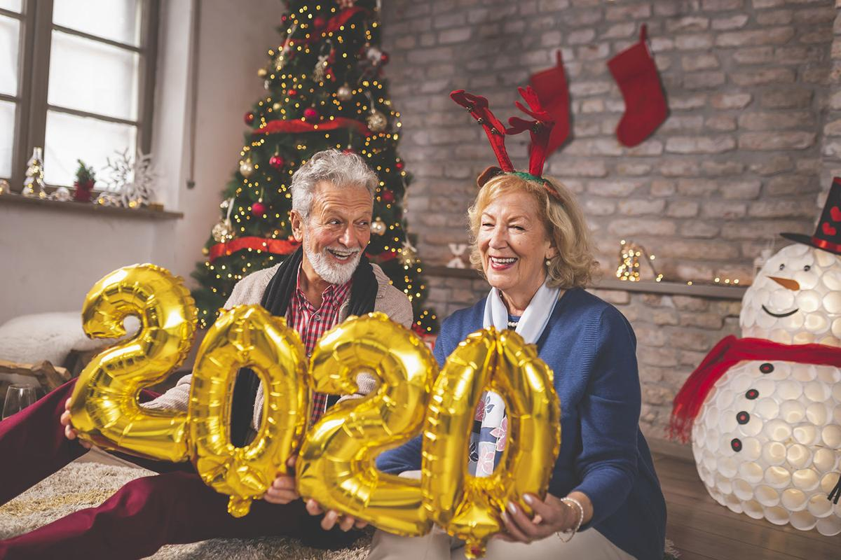 Senior couple holding balloons 2020 on New Year day